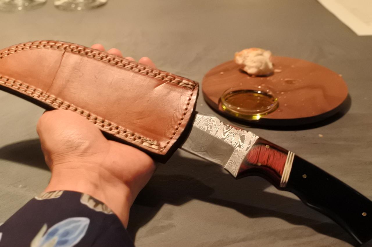 画像: 革製の鞘にからナイフを取り出す