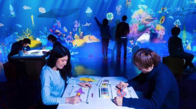 画像: お絵かき水族館 / Sketch Aquarium チームラボ, 2013 この水族館は、みんなが描いた魚たちが泳ぐ水族館です。 「紙」に自由に魚の絵を描きます。すると、みんなが描いた魚と共に、目の前の巨大な水族館で、その魚たちが泳ぎ出します。自分達の描いた魚に触ることもでき、触られると魚は、いっせいに逃げ出します。エサ袋に触ることによって、魚にエサをあげることもできます。 www.team-lab.net