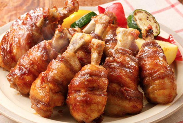 """画像: ミニ黄金マンガ肉 ■材料(2~3人分) ・鶏手羽元 6本 ・豚バラ薄切り肉 6枚(約120g) ・エバラ黄金の味 大さじ4 ・サラダ油 適量 ・付け合わせ ズッキーニ(輪切り)、パプリカ(一口大)、じゃがいも(一口大)、適宜 ■作り方 (1) 鶏手羽元は細い方の骨が見える側にハサミを入れ、骨と身を切り離し、筋を切りながら上の方に押し上げてチューリップ型にします。 (2) (1)に豚バラ薄切り肉をらせん状に巻き付け、耐熱皿にのせ、ふんわりラップをして電子レンジ(600W)で約4分加熱します。 (3) フライパンに油を熱し、(2)を転がしながら焼き、「黄金の味」でからめ焼いたら、できあがりです。お好みで焼いた""""付け合わせ""""を添えてお召しあがりください。"""