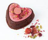 """画像: 毎年バレンタインの期間限定で登場するハートの形の「ガトーショコラ」も、日持ちのする焼き菓子として人気の逸品です。エクアドル産カカオ70%のチョコレートを贅沢に使用した濃厚でビターな味わいは、""""チョコレートではない、けれどチョコレートがしっかり味わえる""""特別な限定感のあるバレンタインギフトをお探しの方にぴったりです。トップには、ホワイトチョコレートをベースにベリーの甘酸っぱさをあしらった愛らしいピンクのハートのチョコレートプレートが飾られ、赤いストロベリー、ラズベリー、クランベリーのコンフィやパウダー、緑色のクラッシュピスタチオが見た目と食感のアクセントとなっていますよ。 ●リンツ・ガトーショコラバレンタイン(サイズ:12cm×12cm) 価格:2,500円(税込) 販売開始は1月下旬より"""
