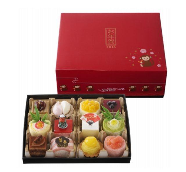 画像: 商品名:「スイーツおせち」 価 格: <9個入>¥2,100(税込¥2,268)、 <12個入>¥2,700(税込¥2,916) 特 長: 抹茶ロールや紅白タルト、獅子舞の飾りをのせたグラサージュフレーズ。スイーツ初めにぴったりなプチケーキのアソートです。おせちのお重をイメージしたパッケージに詰め合わせました。