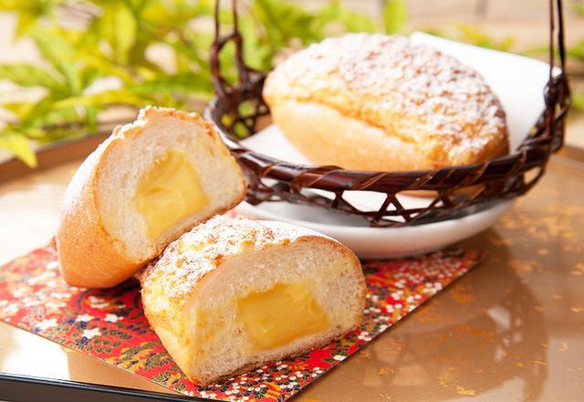 """画像: ◆パン・オ・トロピック 250円(税込)【期間限定】 フランス語で""""トロピック""""(=トロピカル)というその名の通り、パッションフルーツ、バナナ、マンゴー、レモンのMIXピューレを使用したトロピカルなクリームパンです。表面にふりかけたココナッツの風味がアクセントになって、南国フルーツの香りをより引き立てます。"""