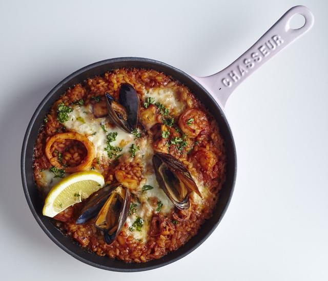 """画像: スキレットリゾット シチリアシーフード 980 円 海老、いか、ムール貝を魚介の旨みが詰まったスープで炊きあげたパエリア風の""""焼きリゾット""""。仕上げにモッツアレラチーズをのせて焼きあげています。"""