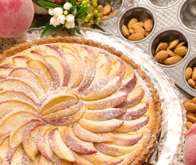 画像: 桃とアーモンドのタルト piece:671円 whole(25cm):6,372円 桃とアーモンドは同じバラ科の植物だということをご存知ですか?同じ種類の風味を持ったこの2つを組み合わせ、タルトを作りました。農家の方は桃を洗ってそのまま皮ごと食べるそうです。それを真似て皮ごと焼き上げてみたら優しい桃色のおいしいタルトになりました。