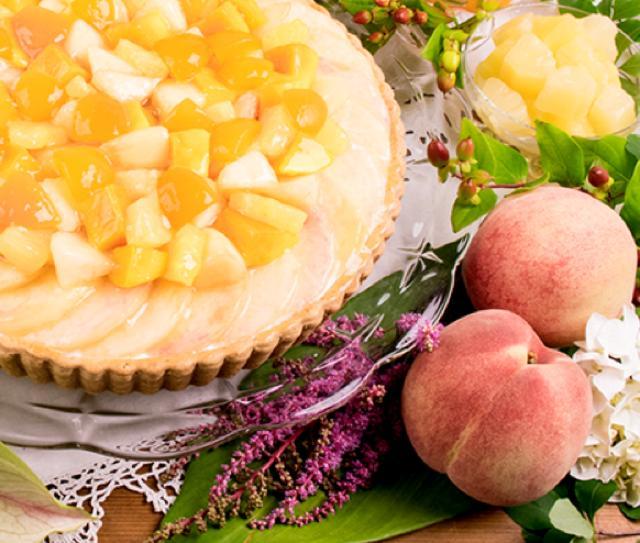 画像: 桃と南国フルーツのタルト piece:691円 whole(25cm):6,588円 桃と果汁いっぱいの南国フルーツをふんだんに飾ったタルトです。カスタードにココナッツ風味の生クリームを重ねた、軽い口当たりのクリームとともにお楽しみください。スポンジに塗った、たっぷりのフルーツジャムのトロピカルな香りがアクセントになっています。