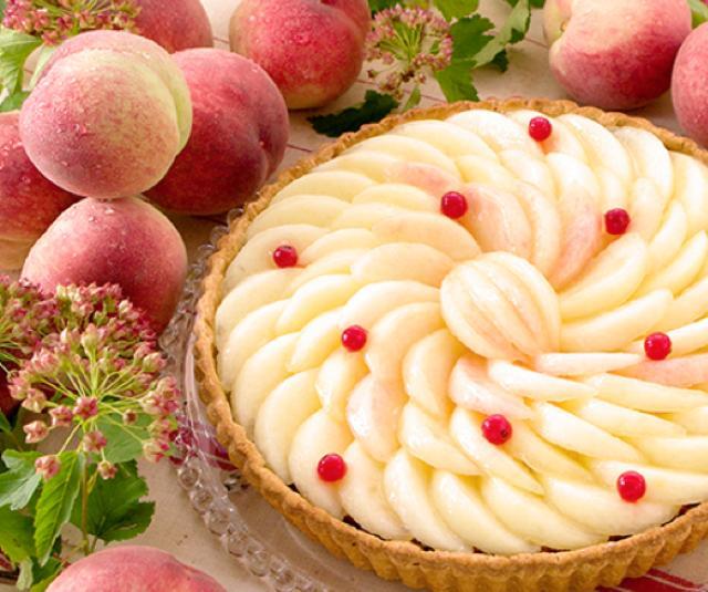 画像: 桃のタルト piece:679円 whole(25cm):6,480円 バター風味豊かな練りパイにカスタードクリームを詰め、甘く果汁たっぷりの旬の桃を贅沢にのせて仕上げました。