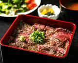 画像: 『熟成和牛のステーキ重』 価格   :980円(税込) 提供数  :毎日ランチタイム10食限定 特長   :(1) 1食あたりのお肉は100グラムです。 (2) 外側はこんがりしっかりと炭火で火を入れ、 中はレアに仕上げ、ブラック&ブルーで焼き上げます。 (3) タレの味は、ほのかに甘味のある オニオンとニンニクのソースとなります。