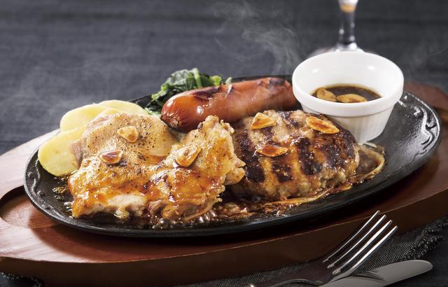 """画像: ■炙りチキンのミックスグリル 1,249円(税込1,348円) 肉厚な身はふっくらと柔らかく、皮目を炎で炙ることで香ばしさを引き出したチキングリル、ジューシーで柔らかな合挽きハンバーグ、プリッとした食感から肉汁がはじけるソーセージを盛り合わせた、""""肉×肉×肉""""のボリューム満点ミックスグリルです。ソースをかければ香りと食欲が湧き立つ鉄板スタイルでご提供します。"""