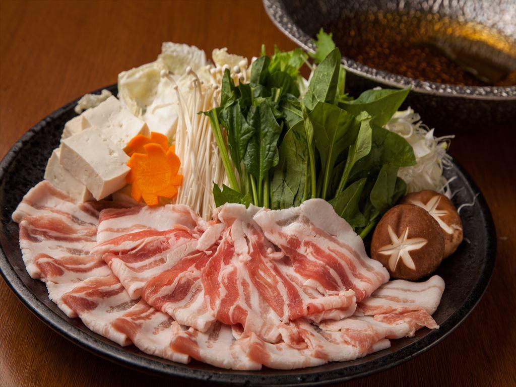 画像: 昆布を加えた九州名物の芋焼酎を鍋に入れ、卓上で温めて「ファイアー」させ、アルコールを飛ばします。そこに蛤をベースにした出汁を加えると魚介出汁の旨みの中に焼酎ならではの深みが加わった、いつもと一味違ったお鍋に変身! 豚の芸術品ともよばれる「鹿児島県産黒豚」のコクや旨味が抜群に豊かな味わいを最も堪能できるしゃぶしゃぶでお召し上がりいただきます。