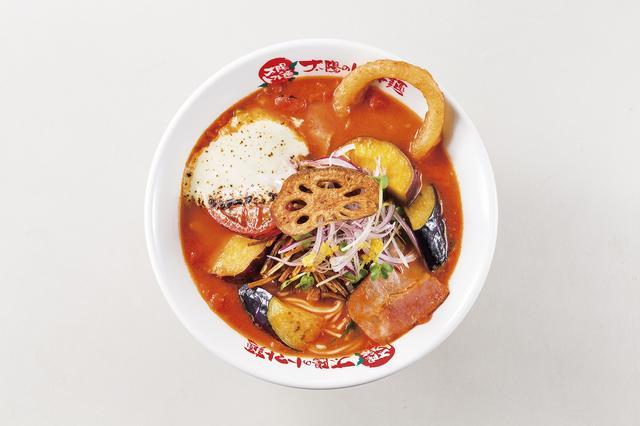 画像: ・商品名:『よくばり野菜のベジトマ麺』 ・販売価格:950円(税込) ・販売期間:2016年12月末予定(年末の営業時間は店舗より異なります。) ・商品特徴:数種類の野菜をふんだんに使用した12月限定のベジトマ麺です。レンコン、オニオンリング、さつま芋、アーリーレッド、カイワレ、江戸菜、茄子、ごぼう、トマトチーズをトッピング。 ごろっごろな野菜の食感、トマトにのせて炙ったゴルゴンゾーラがスープに溶け出しコクを与え、さらに自家製のレモンフレーバーEXVオイルでスッキリまとめた一杯です。