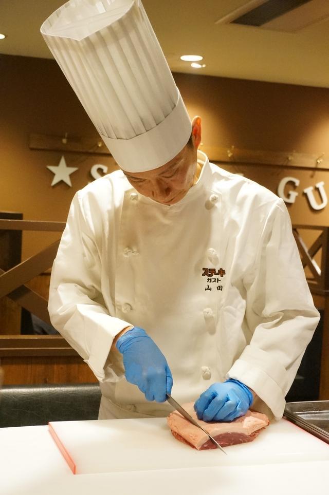 画像: 店舗で塊肉から手切りで一枚ずつ切り出します。 試食会ではシェフによるイチボ塊肉カッティングの実演が行なわれました。