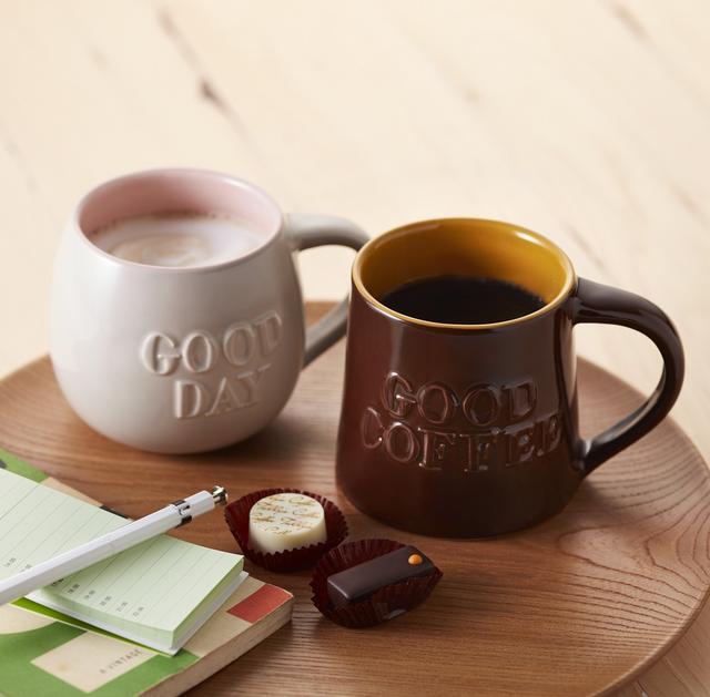 """画像: (写真左) 「グッドデーマグ(ミルクグレー)」 (写真右) 「グッドコーヒーマグ(ブラウン)」 各1,350円 表面に描かれているのは、2つ合わせて""""美味しいコーヒーを飲んで、素敵な1日を過ごしましょう""""というメッセージです"""