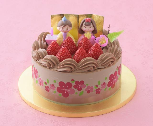 画像: 価 格: 直径15cm、5~6人分/¥2,900(税込¥3,132) 特 長: チョコ生クリームと苺ジャムをココアスポンジでサンド。まろやかチョコ生クリームで仕上げて、おだいりさま&おひなさま、粒より苺を飾りました。苺ジャムの甘酸っぱさがおいしさのアクセント。チョコ好きの方におすすめしたいひなケーキです。