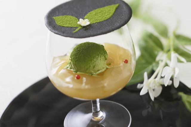 画像: お席についたら、まずはパティシエからのおもてなしの一皿「ヴェリーヌペーシュ」をご提供。さっぱりとした甘みの白桃のコンポートとジュレに、ほろ苦い抹茶のアイスクリームをあわせたパティシエ渾身のアヴァンデセール。グラスの上には、愛らしい茶花の模様をあしらった竹炭のラングドシャを添えて。「和×洋」の絶妙なマリアージュをお届けいたします。
