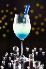 画像: 【5・6月限定】スピカ 春の大三角のひとつである、おとめ座の1等星「スピカ」。別名「真珠星」とも呼ばれる青白く輝くスピカを、白ワインベースのカクテルに、スポイトにはいったブルーシロップをゆっくり絞ると完成する、美しい2層のカクテルで表現。小瓶の中の、真珠に見立てたアラザンシュガーとハートのチョコレートを添えて。