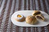画像: ◆コーヒーブール 240円(写真右) コーヒークリームとあんこをスイートロールで包み、表面にクッキー生地をかぶせて焼き上げました。仕上げにコーヒーシュガーをまぶし、外はサクサク、中はふんわりした独特な食感がたまらないパンに仕上がっています。 ◆紅茶のクリームパン 220円(写真左) パンの中に紅茶風味のカスタードクリームをいれ、アプリコットを上に添えて焼き上げました。上品な味わいがクセになるクリームパンです。