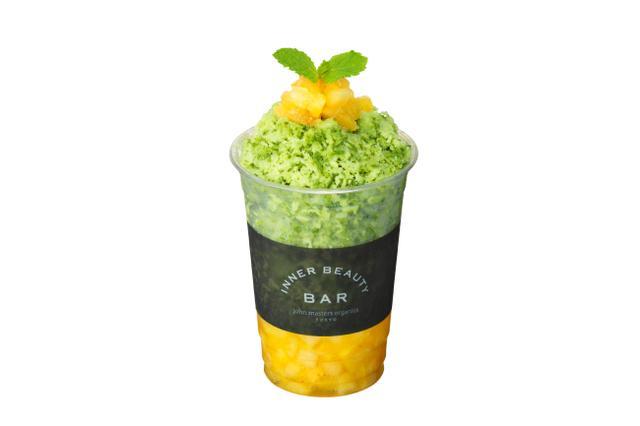 """画像: Organic Shave Ice  MATCHA MORINGA 商品名称  オーガニックシェイブアイス マッチャモリンガ 商品価格  800円(税抜)/ 864円(税込) 抹茶・モリンガシェイブアイス / パイナップル NYでもスーパーフードとして定着している抹茶と注目のモリンガに、オーガニックミルクをミックスしたかき氷。京都産の有機茶葉を使用した抹茶は、茶葉収穫の20日以上前から日光を遮断し光合成を止めることで成分を凝縮。デトックス効果の高いクロロフィルが増量し、血流を促進して冷えの予防にも最適だと言われる、旨み成分のテアニンを豊富に含みます。茶葉をすりつぶしてすべて摂取できる抹茶は、ビタミン類や活性酸素を除去するカテキン、腸内環境を整える食物繊維など、豊富な栄養素を効率的に摂取できます。 沖縄県産のモリンガは、すべての必須アミノ酸を含む唯一の植物で、人間に必要な多くの栄養素がバランスよく含まれていることから、別名""""Miracle Tree(奇跡の樹)""""とも呼ばれています。整腸作用が期待できるギャバ、抗酸化作用の高いポリフェノール、カルシウム、鉄分、各種ビタミンやミネラルなど、圧倒的な栄養価を誇る注目素材です。 さらにビタミンBやCが日焼け対策やアンチエイジングに効果的なパイナップルを贅沢に使用。グリーンとイエローのコントラストが夏の気分を盛り上げます。"""