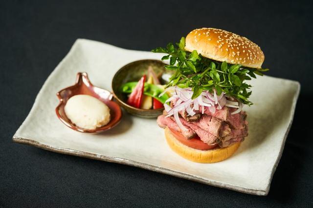 画像: 豪州産ローストビーフバーガー ¥2,480 (鉄板焼 開化屋) 1 時間以上じっくり鉄板火入れした極旨豪州 産サーロインのローストビーフが何枚も重なっ たボリューム満点の一品。ローストビーフのピン ク、オニオンの白、クレソンの緑、トマトの赤。 見た目にも爽やかで噛むほどに肉のうまみが 広がる、上品な味わいのバーガーです。
