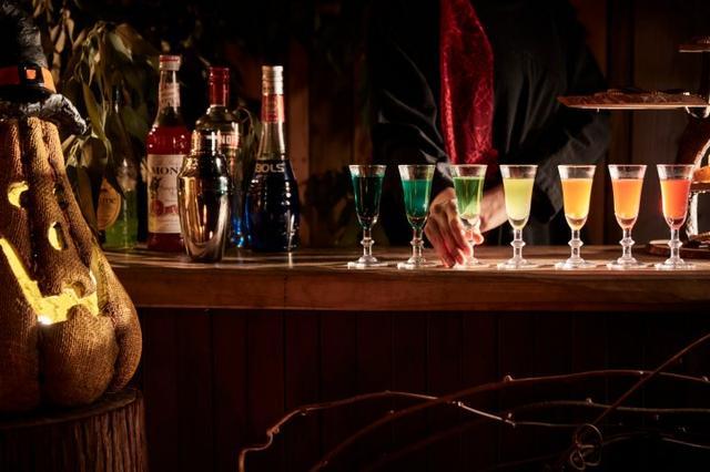 画像: ドリンク 「魔法のカクテル」「魔女の大鍋サングリア」 森の入り口にあるカウンターでは、魔女に扮したスタッフがウェルカムの気持ちを込めて、「魔法のカクテル」をサーブします。オレンジジュースやブルーキュラソーなど5種の材料をひとつの容器に入れて作るこのカクテルは、アルコールの比重の差を活かすことで、グラスへ注ぐ度に色が変わります。ひとつの容器から7色のカクテルが出てくるその様子は、まるで手品を見ているかのようです。また、この不思議なカクテルを飲むことで、魔女の森に迷い込んだような気分を体験できます。 また、ハロウィン気分をさらに楽しみたい方のために、「魔女の大鍋サングリア」も用意しています。シトラスとリンゴを使って作るホットサングリアで、グツグツと音を立てている直径約30cmの大鍋を、魔女に扮したスタッフがかき混ぜて作ります。