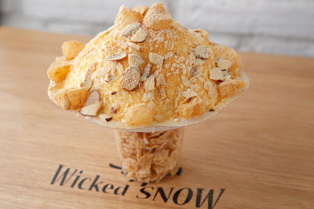 画像: <商品名> ウィキッドゴールド(きなこ) <特徴> 練乳、ミルク、生クリームを独自ブレンドした氷を使用し、口溶けの良さを追求したパウダースノーのようなふわっふわっ食感のかき氷に「厳選したきな粉」と「わらび餅」を贅沢にトッピング。夏の季節にぴったりのかき氷となります。 <価格> 700円