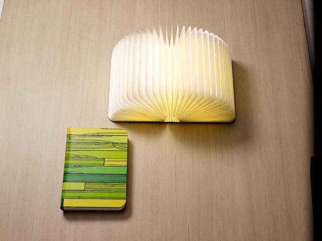 画像: ■Lumiosf ブックランプ Richard Woods 税抜販売予定価格: 37,000円 閉じているときは木製の表紙が美しいハードカバーブックのように見えるLumiosf(ルミオ エスエフ) ブックランプに、MoMA限定のRichard Woodsによる新作が登場。開くと高機能LEDが明るく輝く立体的なランプへと早変わりします。ルミオは、ミニマルでコンパクトなフォルム。半透明のプリーツ状のインテリア部分は、丈夫で耐水性の高いタイベックを使用しています。ベッドサイドや庭でのバーベキューなど、さまざまな用途に使える画期的なランプです。