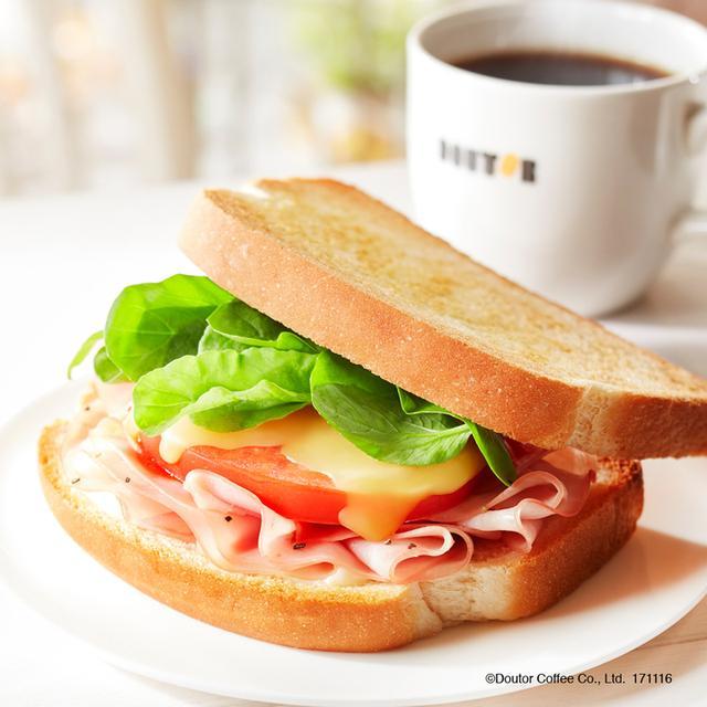画像: 寒い冬の朝に嬉しい、ホットサンドの朝カフェ・セットが新登場。 定番人気のハムとチーズの組み合わせに、国産トマトのうまみを凝縮したトマトソースを合わせました。 温めた後にベビーリーフをトッピングすることで、みずみずしさもプラスしています デンマーク産のゴーダチーズのクリーミーな味わいと、国産トマトソースのさっぱりとした後味を楽しめるサンドイッチです。