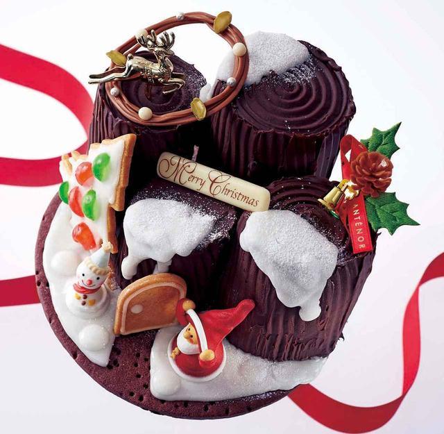 画像: 【商品名】ブッシュの森の家 【サイズ】 直径17.5cm 【価格】¥5,000(税込¥5,400) *予約限定商品。 【ご予約期間】12/15(金)まで 【お渡し期間】12/21(木)~25(月) 【商品説明】 チョコクッキーのお庭に広がるのはフランボワーズの甘酸っぱさをきかせたコクのあるチョコレートの切り株ケーキ。クリスマスツリーを飾ってサンタがお出迎えです。