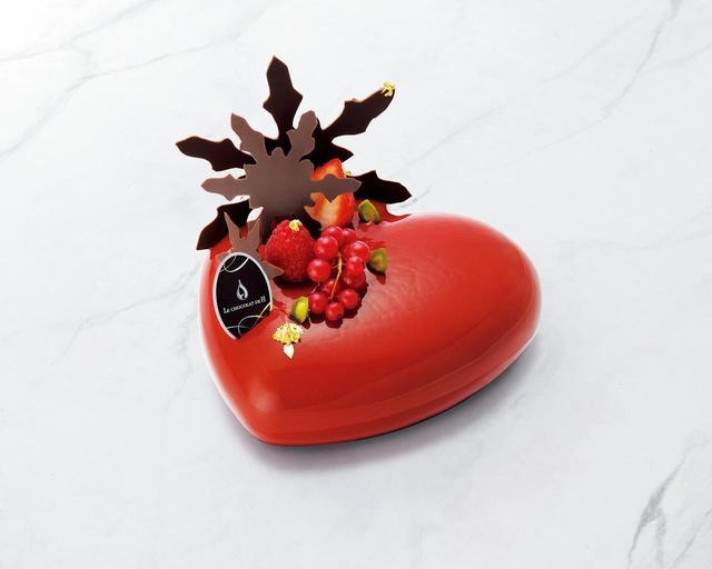 画像: ノエル ヒカリエ(渋谷ヒカリエ ShinQs店限定) ショコラムースの中に相性の良いピスタチオとラズベリーを合わせました。赤くコロンとしたハートのフォルムとル ショコラ ドゥ アッシュならではのチョコレート細工が華やかな仕上がりのケーキです。 限定数: 150台 サイズ: 直径14.5×H5cm 価格 : 5,400円(税込)