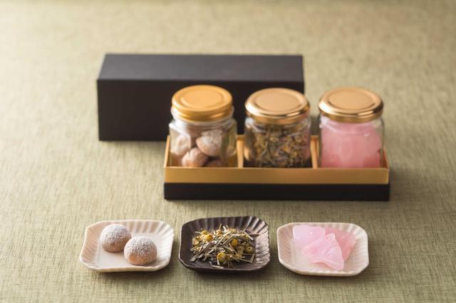 """画像: 【新作】春合わせ/2,600円 珀糖、ハーブティー、ブールドネージュをそれぞれ瓶に詰めたセット。 琥珀糖は、長年親しまれてきた和菓子の食材""""寒天""""を使った砂糖菓子です。このたびのギフトでは桜の花びらをシロップづけにし、香りのエッセンスを加えた商品に仕上げました。ブールドネージュはフランス語で「雪の玉」を意味するクッキーで、雪玉のように口の中でホロホロと崩れる食感が特徴です。黄粉(きなこ)と和三盆を使用し和テイストでご用意しました。これらに加えてご自宅でもこのフレーバーを味わってみたいとお声の多かった、ガーデンラウンジ「坐忘」オリジナルブレンドのハーブティー(カモミール、ラヴェンダー、レモングラスのブレンド)を瓶に詰め、可愛らしい贈り物に仕上げました。"""