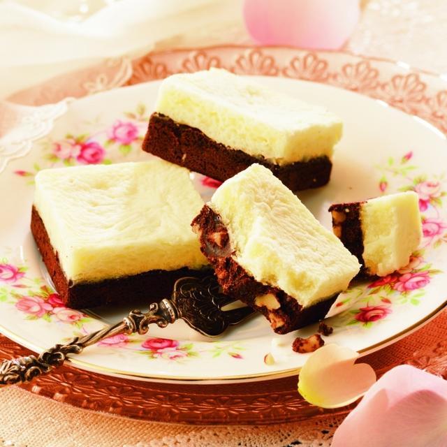 画像: 商品名:チーズ&チョコブラウニー 内容量:3個 価 格:780円(本体価格) 商品紹介: ジンで風味付けしたカカオの香り豊かな生地にクルミを入れて、チーズなどを練り込んだ味わい深い生地をのせて焼き上げました。ジンの香り、チーズのほど良い酸味と香ばしさは、コクのあるチョコレートと相性ぴったりです。 www.royce.com