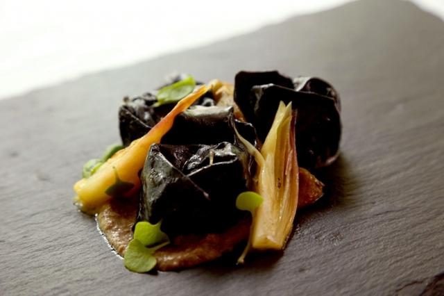 """画像: 3.パスタ~ナチュラルブリッジ~ 岩魚のコンフィとジンジャーで炊き上げたジャガイモのリピエーノ 黒いトルテッリーニ ローストしたグリーンパプリカとミョウガを添えて   2,200円(税抜) ジンジャーとローリエで作ったハーブティーで炊き上げたジャガイモとコンフィにした岩魚をピューレ状にし、イカスミを練り込んだ黒いパスタの生地で包み込んだリピエーノ※。 """"妖精の棲む洞窟の香り""""を纏った、安らぎを感じさせながらも凛としたニュアンスを表現した一皿です。 使用ハーブ:ジンジャー、ローリエ ※リピエーノ=詰めものをした料理の総称。"""