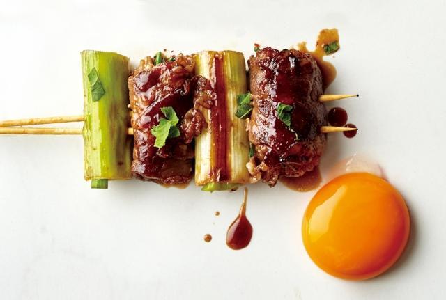 """画像: ・日本の""""すき焼き""""が串刺し!「スキヤキ侍」 えのき茸とクレソンを牛肉で巻いて、割り下風の醤油だれを絡めた「スキヤキ侍」串。卵黄を絡めて。"""