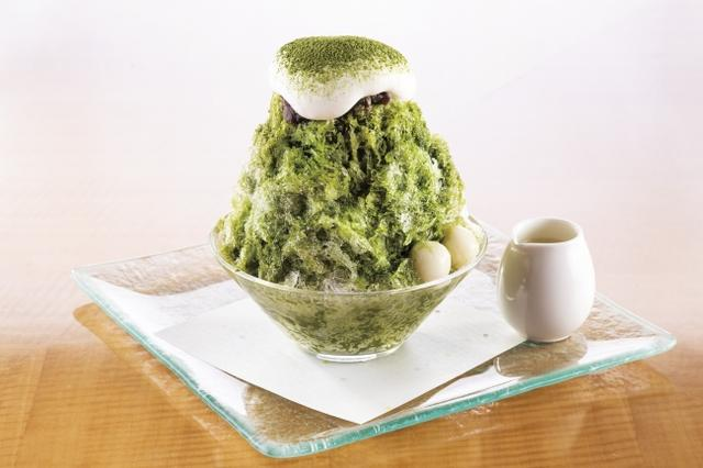 画像: かき氷の定番、日本の涼を呼ぶ抹茶のかき氷。抹茶、小豆、白玉など和の素材を組み合わせた王道の宇治金時をホテルならではのアイデアを添えてご提供いたします。始めに抹茶のアイスを氷で閉じ込め、ほろ苦い宇治抹茶のソースを回しかけます。最後に大納言と氷との相性を考えて柔らかくホイップした生クリームをかけ、香り高い抹茶パウダーで仕上げます。そのままで頂いても別添えの練乳足しながらより甘さとクリーミーさを加えて楽しむ のもおすすめです。午後のはんなりとしたひとときを演出してくれる氷スイーツです。