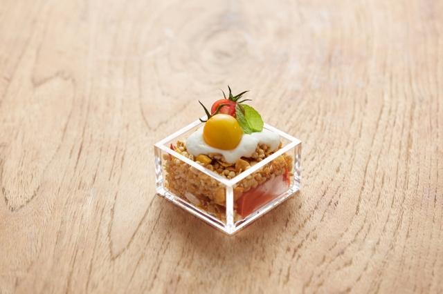 """画像: トマト豆腐と""""フルーツグラノラ ハーフ""""のシメグラノラ(税別399円) プチトマトがトッピングされた姿は、スイーツとは思えない見た目。フルーツ グラノラ ハーフとヨーグルトソースの甘みに、トマトの爽やかな酸味を加え、食欲が落ちやすい夏にもペロリと食べられる新感覚な逸品に仕上げました。"""