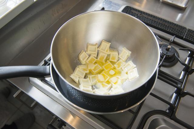 画像: ①チョコレートとバターを湯煎にかけて溶かす。(フライパンに湯を沸かして火を止め、チョコレートとバターを入れたステンレスのボウルを湯の中に入れて10分置く)