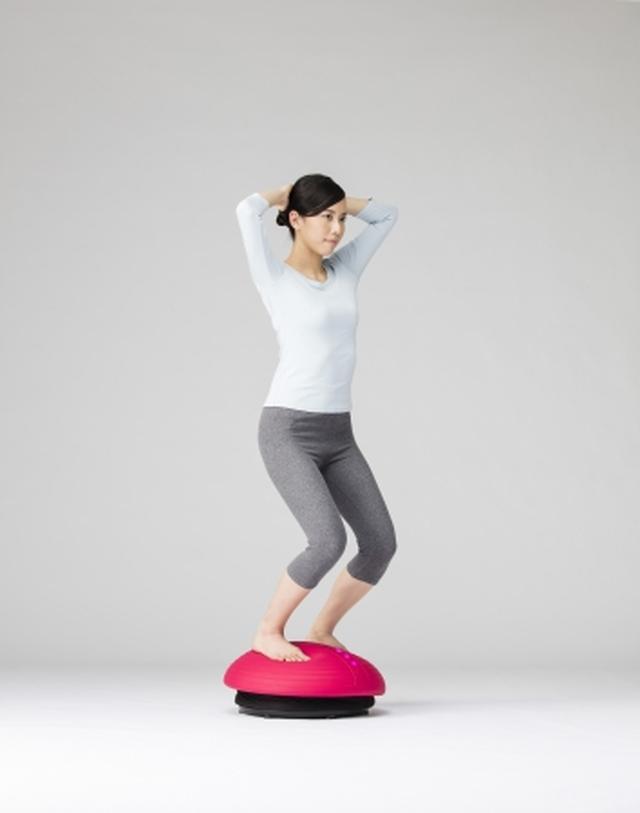 画像: 腕を頭の後ろに組み、ひざを曲げる
