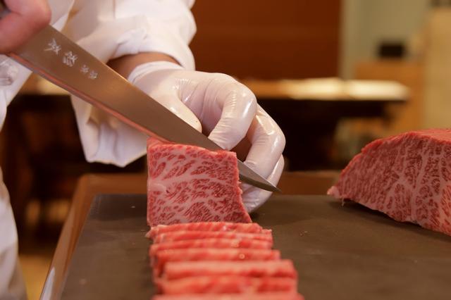 画像: カウンター前のオープンキッチンで行われる肉切り
