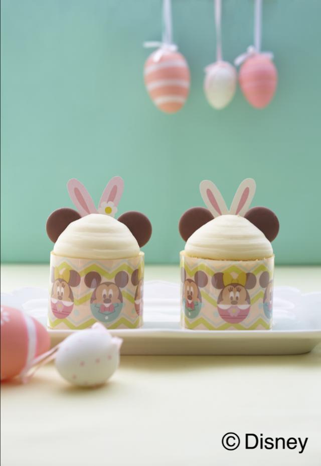 画像: 【イースター ミッキーマウス&ミニーマウス ケーキ】 ふんわりとしたスポンジ生地に、ホイップクリームを塗り広げて黄桃をちらし、ロールケーキを作ります。ロールケーキの上には、カスタードクリームをのせ、丸いミルクチョコレートをトッピング。オリジナルのうさぎの耳のピックをあしらい、イースターエッグのデザインのフィルムを巻いて、「ミッキーマウス」と「ミニーマウス」のケーキに仕上げます。ケーキは1人4個お持ち帰り。みんなでケーキを囲めば、4月21日のイースターがさらに盛り上がること間違いなし!