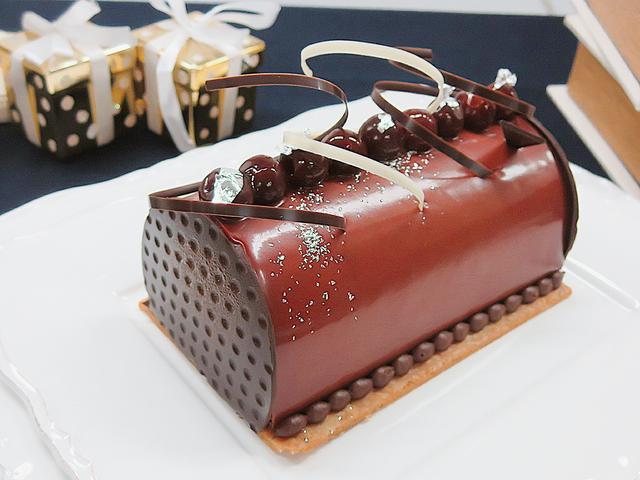 画像: 【ビュッシュ・ショコラ・ヴァニーユ】 大人向けの本格的なチョコレートクリスマスケーキです。ふわりとした軽やかなムースとクリームの中にキルシュ漬けした甘酸っぱいグリオットチェリーとソテーした洋梨が入っています。