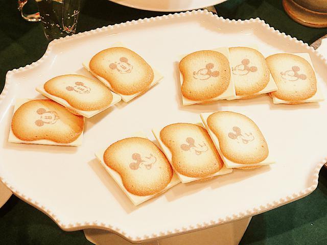 画像: ミッキーがプリントされたラングドシャクッキーに、はみだしサイズのショコラをサンドしました。ショコラはバナナミルクシェイク味です。あまいバナナの香りがします。東京土産としてオフィスでも配りやすい個装タイプです。 © Disney