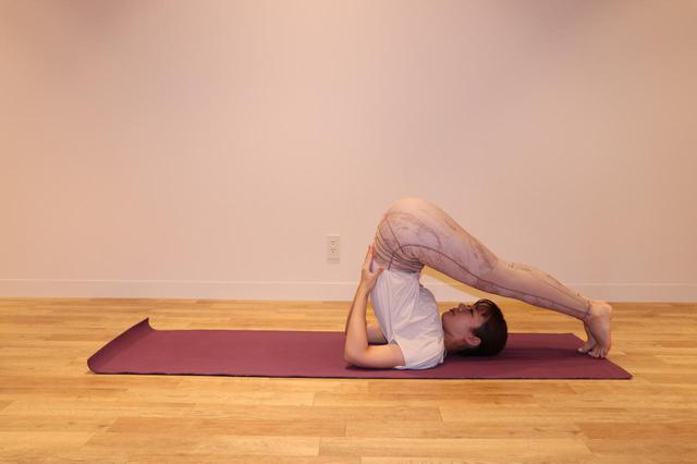 画像: ③息を吐きながら、両脚を頭の先に伸ば す。この状態で 5 呼吸キープ。
