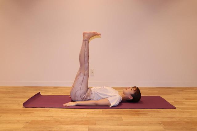 画像: ①仰向けになり、両脚をそろえて上 に持ち上げる。両手は体側へ伸ばす。