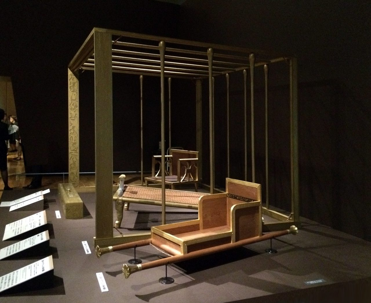 画像: 手前「王妃ヘテプヘレスの輿(複製)」、奥に「「王妃ヘテプヘレスの天蓋(複製)」、王妃ヘテプヘレスの寝台(複製)」、「王妃ヘテプへレスの肘掛椅子(複製)」すべてモナコ グリマルディ・フォーラム所蔵。 原品はいずれも古王国・第4王朝時代  スネフェル王~クフ王治世(前2614~前2556年頃)。カイロ・エジプト博物館所蔵  (C)cinefil art review