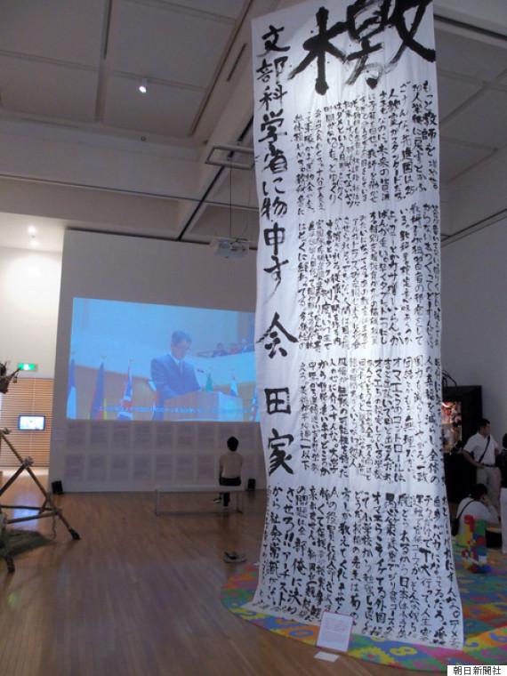 画像: 天井からつるされた作品が「檄文」。背後は映像作品「国際会議で演説をする日本の総理大臣と名乗る男のビデオ」=25日午前、東京都江東区の都現代美術館 http://rdsig.yahoo.co.jp/media/news/medianame/articles/RV=1/RU=aHR0cDovL2hlYWRsaW5lcy55YWhvby5jby5qcC9saXN0Lz9tPWFzYWhp;_ylt=A7dPJopEGbNVW30AWVjyluZ7