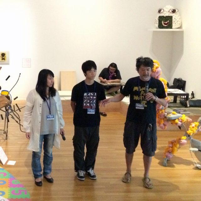 画像: 作品解説する「会田家」。奥に写っているのは、会場でリアルタイムで製作する会田氏の絵を木版にする彫り師の方。(C)cinefil art review
