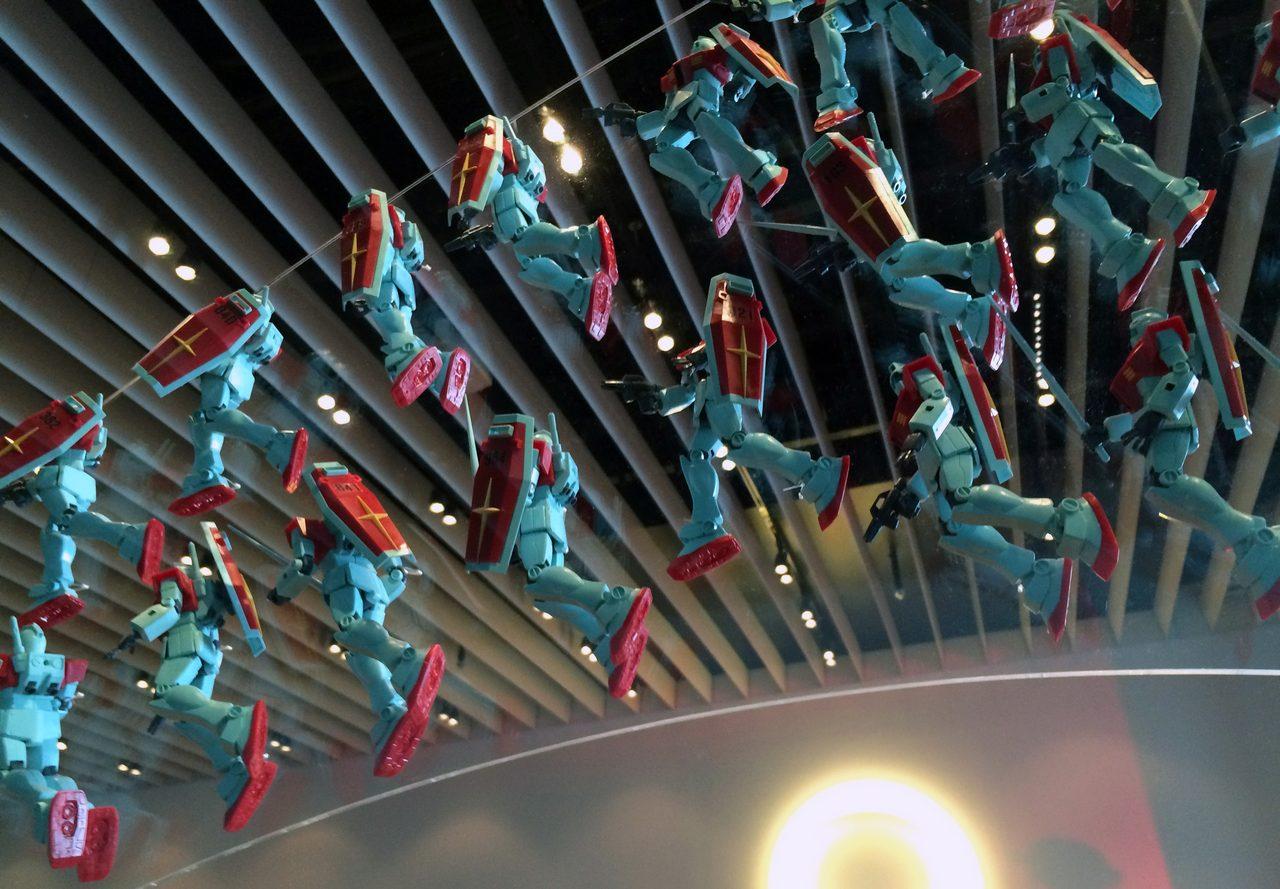 画像: 昨年の、大阪会場での「ガンプラ大作戦」で制作されたガンプラ1000体の展示の一部。番号が付いていて、制作した人には、どれが自分のものか分かるという憎い演出 photo(C)cinefil art review