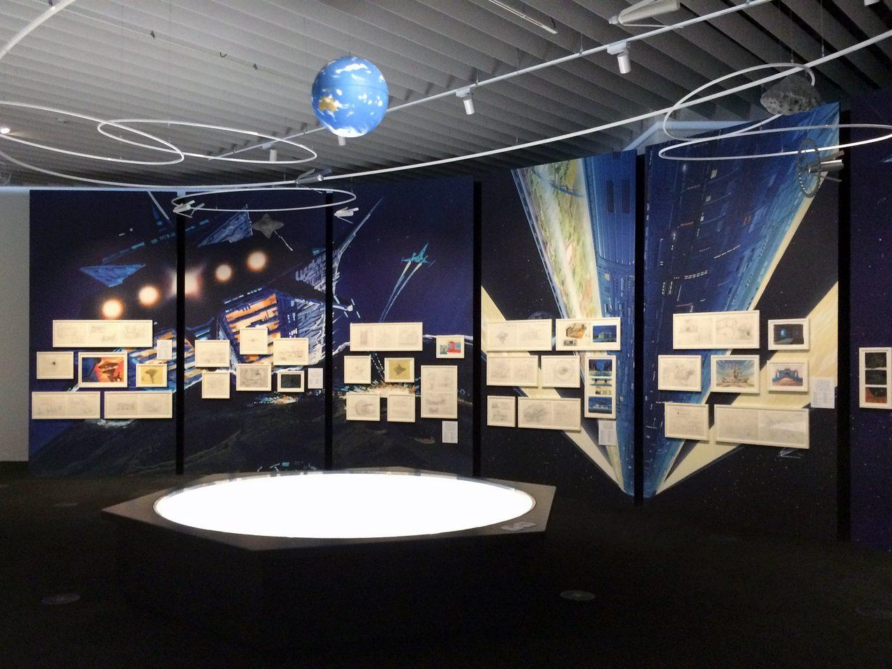 画像: 天井には、ガンダムの世界観と地球やスペースコロニー・宇宙要塞などの位置関係を再現したモデル。 photo(C)cinefil art review
