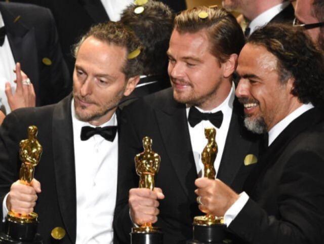 画像: イニャリトゥ監督などとオスカー像を片手のディカプリオ