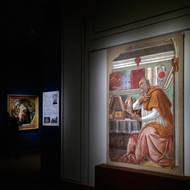 画像: 右手前:書斎の聖アウグスティヌス(あるいは聖アウグスティヌスに訪れた幻視) サンドロ・ボッティチェリ 1480年頃 剥離されたフレスコ画 ©フィレンツェ、オニサンティ聖堂 左奥:聖母子、洗礼者聖ヨハネ、大天使ミカエルと大天使ガブリエル サンドロ・ボッティチェリと工房 1485年頃 テンペラ/板 ©フィレンツェ、パラティーナ美術館