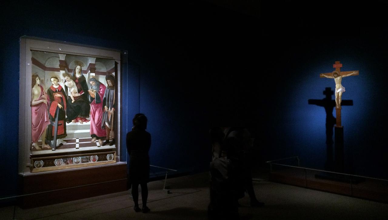 画像: 左:玉座の聖母子と聖セバスティアヌス、聖ラウレンティウス、福音書記者聖ヨハネ、聖ロクス(中央画) 聖アウグスティヌス、聖ラウレンティウス、聖アンブロシウス、聖フランチェスコ、ピエタのキリストの描かれた5つの円形区画、聖ラウレンティウスの物語2場面(裾絵) サンドロ・ボッティチェリと工房 1499年 テンペラ/板 ©モンテルーポ・フィオレンティーノ、サン・ジョヴァンニ・エヴァンジェリスタ聖堂 右:磔刑のキリスト サンドロ・ボッティチェリ 1496-98年頃 テンペラ/板 ©プラート大聖堂付属美術館(サン・ドメニコ壁画美術館に寄託)